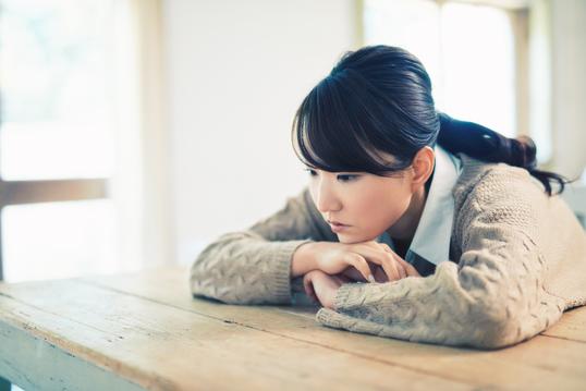 机にもたれかかり少し休んでいる女性