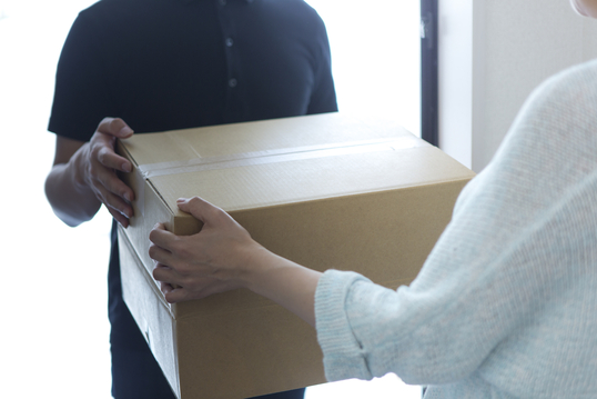 玄関先で荷物を受け取り代引きで支払いをするイメージ