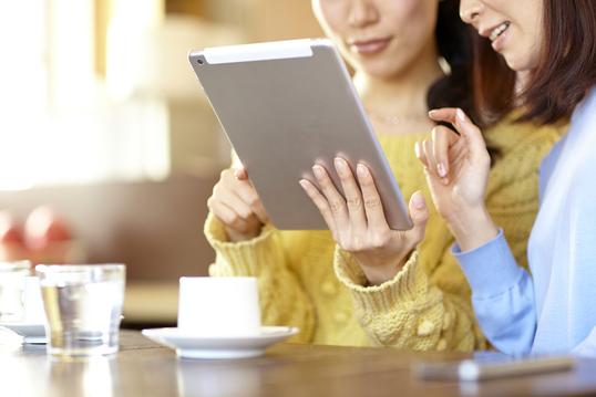 タブレットを手に見入っている2人の女性