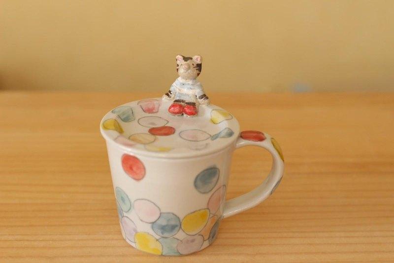 有盒蓋的五顏六色的小點杯子與貓。