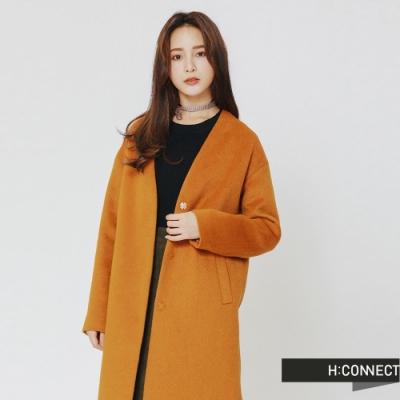 毛呢質料與暗釦設計質感加分 兩側口袋設計增添穿著方便性 簡約純色打造知性都會感