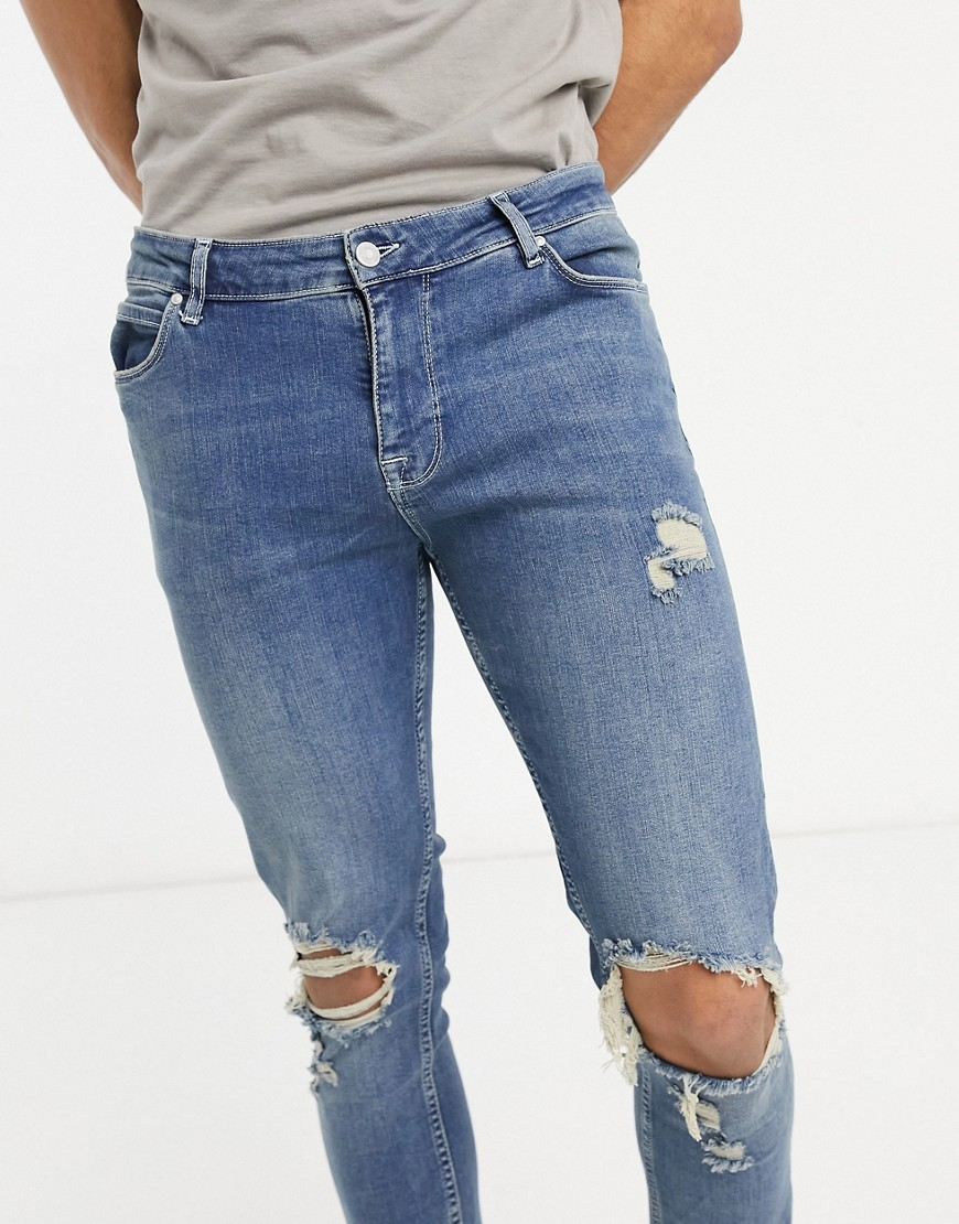ASOS DESIGN skinny jeans in dirty mid wash blue with rips