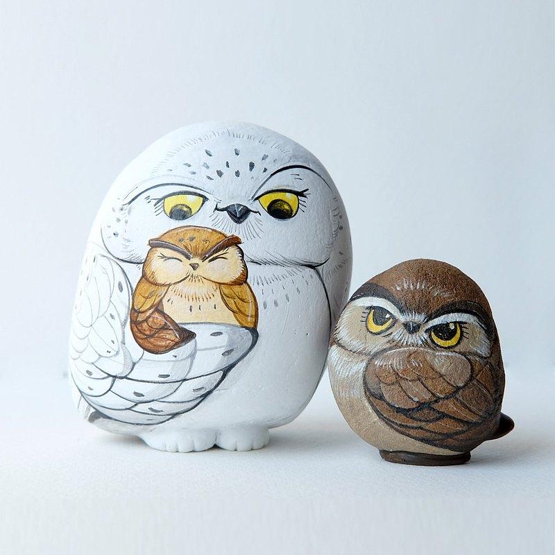 貓頭鷹石畫(雪貓頭鷹媽媽和兒童棕色貓頭鷹)。