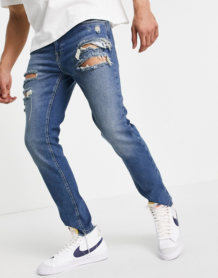 ASOS DESIGN skinny jeans in tinted dark wash with heavy rips-Blue